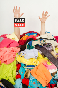Man hands with the sale sign reaching out from a big pile of clo